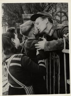 A German soldier, captured by the Third U.S. Army, leans over the railings of a temporary prisoner-of-war cage in Worms to bid farewell to his wife and son before being transported to the rear. Worms, nine miles north of Ludwigsshafen on the west bank of the Rhine, fell to the Americans March 20, 1945. From March 14 to 25, the third U.S. Army took 76,997 prisoners.