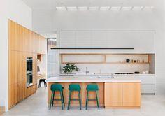 As banquetas coloridas criaram contrastes cheios de vida e descontração junto à marcenaria desta cozinha! O projeto é do escritório Robson Rak Architects. Foto: Lauren Bamford.