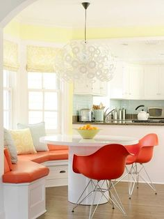 This curved red banquette has an air of boldness. Combined with the kitchen's white cabinetry and light yellow walls, the red bench cushion and chairs have a distinct modern feel. The statement-making mod light fixture adds another fun element.