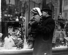 A father gives his child a lift to better view the Christmas goodies, c. 1910. iChi-37800. #chicago #history #holidays #christmas