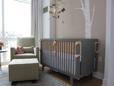 White tree wall accent is paired with leaf mobile for a woodsy theme in this nursery, featuring grey wood crib next to sharp lighter toned armchair and matching cube ottoman.