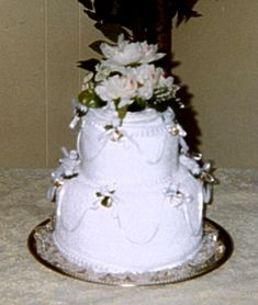 Fake Wedding Cake    By RushÂ'd Lady, 2004  Materials:    14 inch cake plate/ tray    3 white bath towels     3 white hand towels    1 pkg white pearl beaded straight pins     1 pkg safety pins    1 yd 1.5 inch wide polyester white ruffled lace    4 yd .5 inch white satin pleated ribbon    2 bushes white silk roses & greenery    green floral tape    1 spool .25 inch wide white picot satin ribbon    2 pkg Wilton Gold Wedding Band Favors    24 white polyester rosebud floral picks with wire…