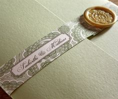 Printed paper belly band for invitation suites, secured with custom wax seal