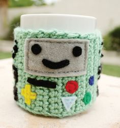 BMO Beemo Video Game System Coffee Mug Tea Cup Cozy: Adventure Time -ish Cartoon Kawaii Crochet Knit Sleeve. $20.00, via Etsy.