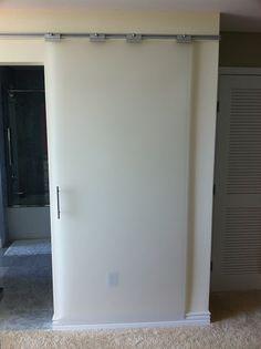 IKEA Besta rails and glass shower door clamps/brackets with plexiglass create a  low cost DIY barn door system.