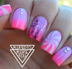 Violet and pink gradient nail art with violet sparkles, beads and swirling white polish details,