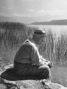 Swiss Psychiatrist Dr. Carl Jung Sitting on Stone Wall Overlooking Lake Zurich. Photo by Dmitri Kessel.