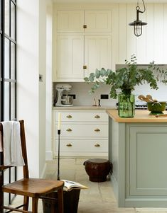 It's the combination of such a light and airy space, the flagstone floor, the pastel painted cupboards and the detail that make this kitchen so charming