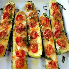 Slice the zucchini in half. Slice off the bottom to keep in stable. Brush with olive oil and top with garlic or garlic powder. Top with sliced tomatoes, salt and pepper to taste. Use mozzarella cheese, Parmesan cheese or mixed blend.. Bake 375 for 20 to 30 minutes until soft