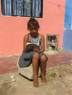 Sponsored child Janina from Barranquilla, Colombia, enjoys some sunshine while she completes her homework.