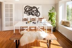 The dining room is a perfect example of balancing modern with antique. Vintage armchairs and a reclaimed wooden bench surround a sleek BluDot table.