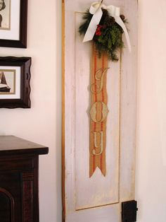 """Marian Parsons uses upholstery webbing, glittered chipboard letters, plus sprigs of greenery and red berries to create this vintage-inspired holiday banner and wreath. """"German glass glitter makes these letters sparkle and will tarnish over time to give the banner a vintage look,"""" she says."""