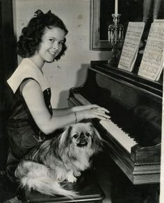 Shirley Temple playing the piano with her dog, Ching Ching II, 1940s.