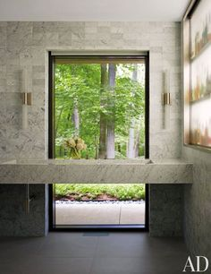 Nickel sconces by Casella Lighting frame the window in a bath in New Canaan, Connecticut; the sink fittings are by Hansgrohe.