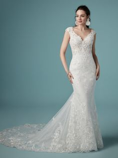 Beaded embroidered lace motifs cascade over Chantilly lace in this soft sheath wedding dress, accenting the illusion double-lace train. The bodice features a delicate V-neckline, sheer cap-sleeves, and scoop back, all accented in beaded lace motifs. Finished with covered buttons over zipper closure.