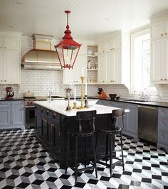 Designer Tommy Smythe combines a graphic Escher-style tile floor, a handsome black island, chalky grey cabinetry and a cherry-red lantern in his client's kitchen — and makes it all work. This design riffs on period kitchens, but is completely contemporary. Tommy notes that the owners didn't want to renovate this kitchen again, so this look needed legs.