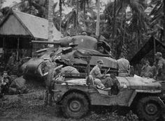 Able Company tankers upload main gun ammo out of a jeep at Volupai Plantation during the New Britain campaign.