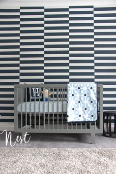 This bold impact wallpaper is such a preppy touch in this darling baby boy nursery!