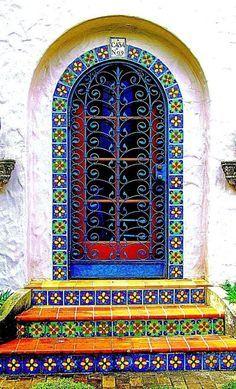 A colorful door surrounded by bright Spanish tiles  | door | doors | door decorations |   https://steeltablelegs.com