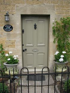 White geranium in vintage stone planters make for a welcoming entrance.