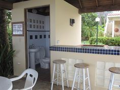 Pool side Covered Cabana with seating area, bar, bath and outdoor shower
