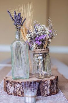 a log slice with lavender, spikes and flowers in jars make a cute centerpiece
