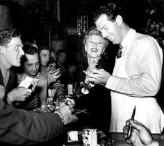 Ginger Rogers and Fred MacMurray cheerily sign autographs for Hollywood Canteen servicemen c. 1940s..