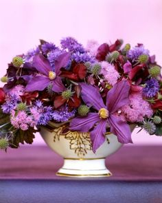 Mauve and Purple Arrangement  A fine French footed porcelain bowl overflows with clematis, ageratum, bachelor's buttons, sweet peas, and leaves of eryngium and heuchera, making a varied and beautiful display of mauve.