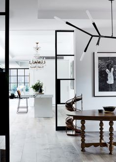 In the dining room are a Spanish table from Holly Hunt and a 19th-century model staircase. Ceramic snake bowl from Safari Living. Artwork by Rex Dupain. A Baccarat chandelier adds sparkle to the kitchen. 'Drexel' barstools from Coco Republic.
