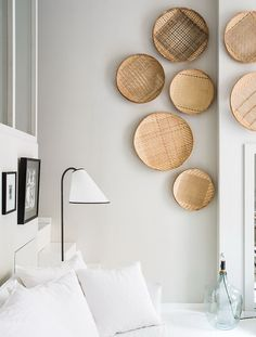 The decor has been designed by French studio and shop Maison Hand. Walls and floors have been kept white to create a spacious effect and the apartment is filled with furniture and accessories made from natural materials such as rattan and wood. Hanging Bookshelves, Baskets On Wall, Hanging Baskets, Cane Baskets, Wall Basket, Hanging Plants, Wicker Furniture, Home And Deco, Wall Spaces