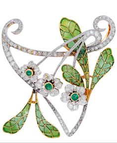 An Art Nouveau Enamel and Diamond Brooch, circa 1905. The delicate trio of florets embellished with emerald pistils and old-cut diamond petals, slender stems and coiling whiplash tendrils, to the green plique-à-jour enamel leaves, mounted in platinum and 18k gold, with pendant loops to the verso, French assay marks.