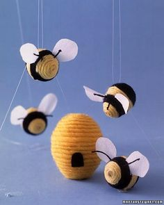 These insects are spinning a yarn about how they came to bee: Glue the end of a strand of yellow yarn to the tip of a quail egg. Once dry, coil the yarn around the egg, alternating yellow and black sections, and gluing as you go. Glue on the wings and antennae, tucking between the strands with a toothpick. For the hive, use a regular egg; the door is cut from felt. Use poster putty to make the hive stand up.