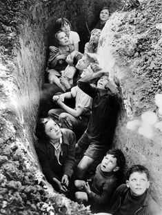 British children huddle together & watch bombers fly overhead.