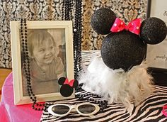 Minnie Mouse Table Decor made using black spray-painted styrofoam balls which were attached with toothpicks, a polka dot ribbon & a feather boa... check out all the other cute Minnie Mouse birthday party ideas!
