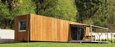 12 Homes Made From Shipping Containers: This perfectly simple, wood clad, absolutely horizontal 40-foot cargo container house sits on a flat site in theGalician countryside ofSpain. Its porch and removable awning allow for outdoor enjoyment, which is ideal since it's a summer house. It was designed by architects Severo Fernández and Basilio Rodríguez of Estudio Base.