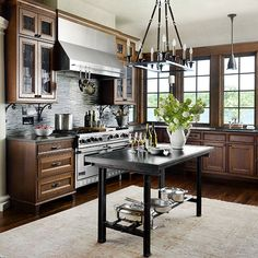 Natural light complements the collection of wood, iron, marble, and granite in this kitchen that's both traditional and modern. A cream colored ceiling lightens the space, which includes richly stained cabinets and black gran