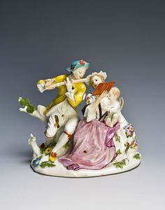 A Meissen musical group, circa 1745.  A gentleman flautist plays to his female companion, who is holding a song sheet whilst feeding an infant at her breast; sitting side by side on a flowering tree stump, he wearing a gilt edged yellow jacket fastened at the neck with a black ribbon, cream trousers secured with a gilt button, a key suspended by a ribbon from his waist, his gilt edged turquoise hat decorated with an iron red flower, his companion wears a puce apron over a skirt decorated