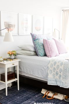 cozy bedroom! Love the prints on the blankets and pillows. plus cool art gallery above bed