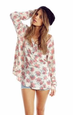 Cozy thermal featuring a scoop neck with henley-style buttons, long sleeves with banded hems, and an extra roomy, a-lined body with a rounded hem.   In Pale Moon Off-White with an allover, sublimated, red floral print.  50% Rayon, 50% Polyester  Model wears a size small.