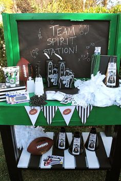 "LAURA'S little PARTY: Show your team spirit with Coca-Cola! Create a team spirit station and include everything your guests will need to cheer on their favorite team! I painted an old potting table in green, black and white. I added a chalkboard back drop and painted ""team spirit station"" with a chalk marker. See our post for more tailgating ideas! #football #tailgate #gameday"