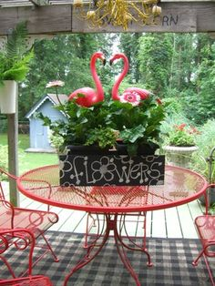 Pink Flamingos and flowers on red patio table!