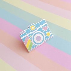 Camera pin badge made of hard enamel in lovely pastel colours. Features cute rainbow detailing with heart and star designs. Measures 2.5cm x 1.9cm. Clutch back.
