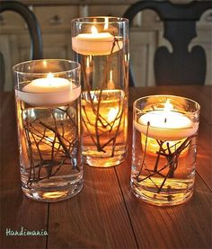 Floating candles in glass containers with branches