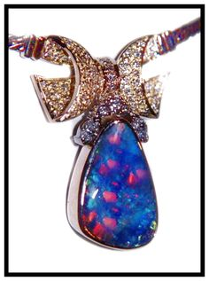 18k gold diamond encrusted bow bezel on top of red on black opal. A feature for ladies fashions and jewelry (jewellery)