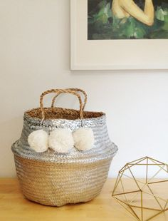Beautiful and practical silver handwoven sea grass basket with white pom poms.  These beautiful baskets have so many uses from an original beach
