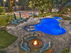 Esta es mi patio trasero y tiene una piscina y una cancha de baloncesto y un spa.