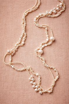 """Cascading from a hammered silver clasp, variegated pearls form eye-catching clusters and rippling patterns. Handmade by Razok, exclusively for BHLDN. 42""""L, 0.5""""W. S-hook closure. Sterling silver, glass pearls. Japan."""
