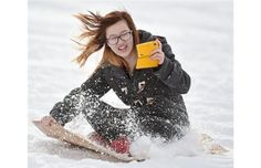 St. Joseph High school student Karen Tang, 16, records her experience as she zips down Connors Hill on a wood sled she made in Shop Class in Edmonton on Friday Jan. 16, 2015. Students in teacher Robyn MacKay's Shop class each were given a word such as: organic, bent, folded, traditional or raw, then has to design and build a sled on those lines, and when completed, they headed outdoors to try them out.