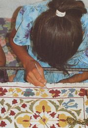 A village woman uses a tambour hook to produce chain-stitch outlines and linear details on a new suzani.