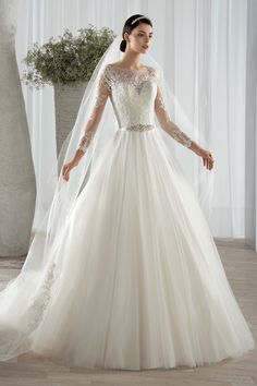 Style 582  This classic tulle, Aline gown with a jeweled belt features delicate beaded lace appliques throughout the bodice, sheer neckline and long sheer sleeves. The embellished sheer back features button closures and is finished with a Chapel length train.